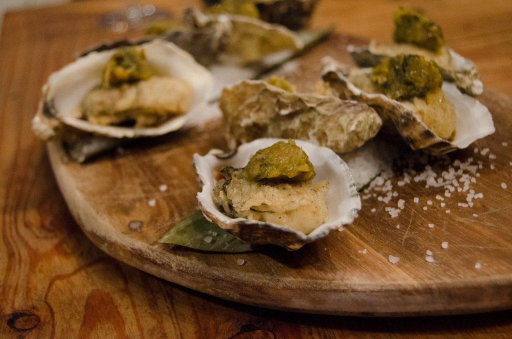 Oesters, jalapeno vinaigrette, paprika compote, houten tafel, houten plateau, zeezout, een bite of in het verrassingsmenu